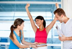 Happy woman at the gym with her trainers measuring her body Ð weight loss