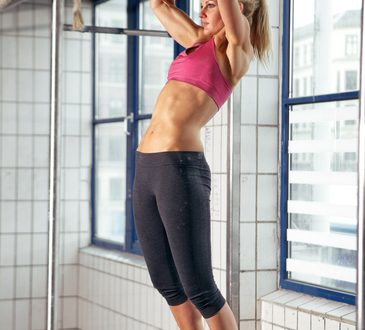 Sexy fit woman performing pull ups in a bar