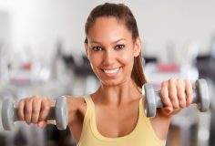Woman working out with dumbbells at a gym