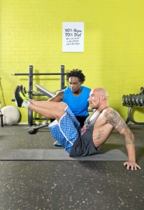 Personal fitness trainier motivating a client, during his workout in a gym, training his abs