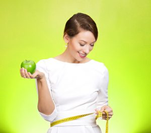 Closeup portrait young attractive, happy, fit woman in white dress, holding lime apple, measuring her waist, isolated green background. Healthy life style, nutrition. Positive emotion, expression