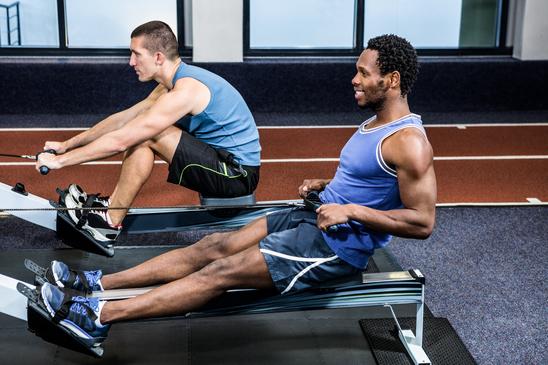 Muscular men using rowing machine at gym