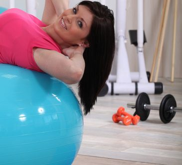 young woman doing stability ball abs exercises in the gym