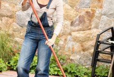 Smiling woman raking leaves autumn fall garden housework
