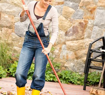 Smiling woman raking leaves autumn fall garden housework