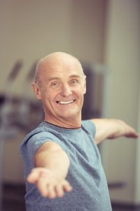 Happy elderly man working out doing exercises