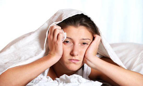 A portrait of a young woman in bed with a cold over white background