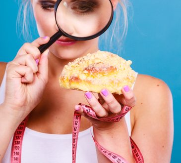 Woman measuring tape around hand checking examine sweet roll bun with magnifying glass. Female with fattening junk food. Bad unhealthy eating nutrition concept.