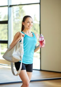 woman with sports bag and bottle of water in gym