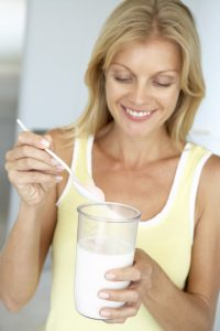 Mid Adult Woman Holding Dietary Supplements