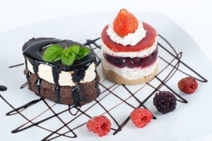 Desserts with chocolate topping and fruit on the plate.