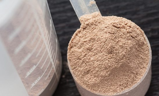 Scope of chocolate whey isolate protein next to the translucent protein shaker, with focus on the protein inside the scoop