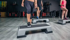 People legs over steppers training in aerobic class