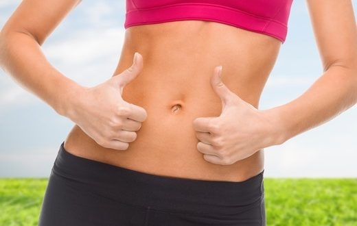 fitness and diet concept - close up of female abs and hands showing thumbs up